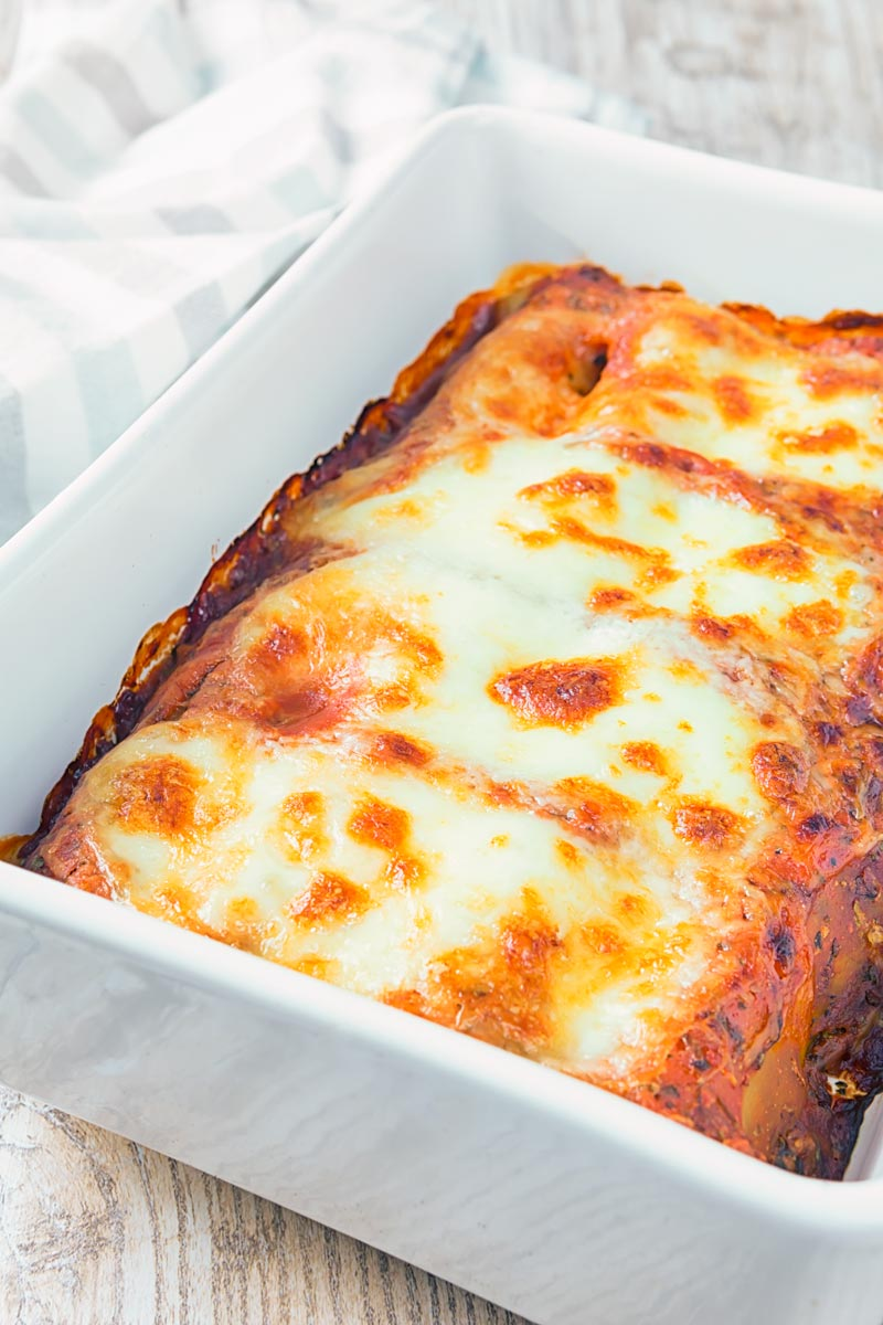 Portrait image of baked Goats' Cheese and Spinach Cannelloni in a white casserole dish