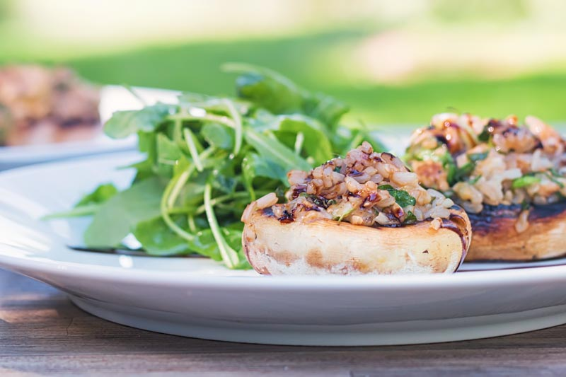 Landscape image of grilled stuffed mushrooms on a white plate with a rocket side salad with a garden scene in the background