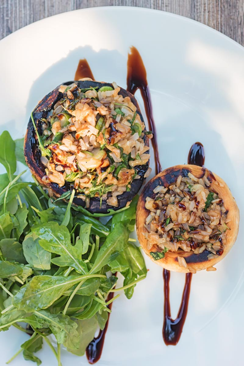 Portrait overhead image of grilled stuffed mushrooms on a white plate with a rocket side salad