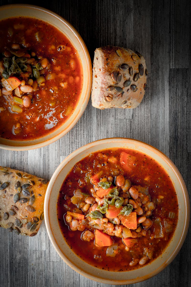 Overhead portrait image of two bowls of tomato and bean soup in earthenware bowls served with a seeded bread roll