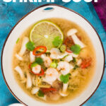 Overhead tall image of a hot and sour shrimp soup with mushrooms and chili and lemon in a clear broth