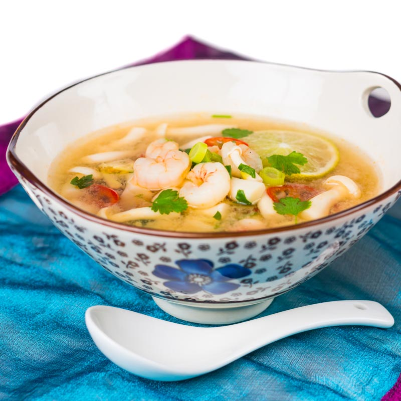 Square image of a hot and sour shrimp soup with mushrooms and chili and lemon in a clear broth in an Asian style bowl decorated with a blue flower