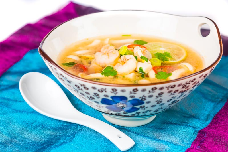 Landscape image of a hot and sour shrimp soup with mushrooms and chili and lemon in a clear broth in an Asian style bowl decorated with a blue flower