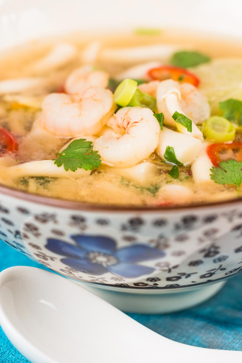 Close up tall image of a hot and sour shrimp soup with mushrooms and chili and lemon in a clear broth in an Asian style bowl decorated with a blue flower