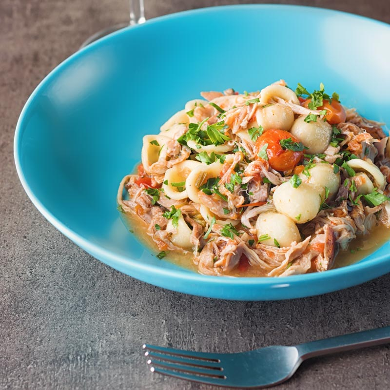 Square image of a light shredded rabbit ragu with orecchiette pasta served in a blue bowl