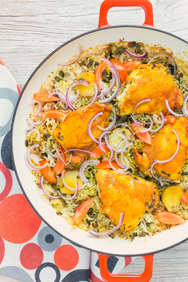 Tall close up overhead image of one pot chicken and rice featuring turmeric chicken thighs and red onion slivers