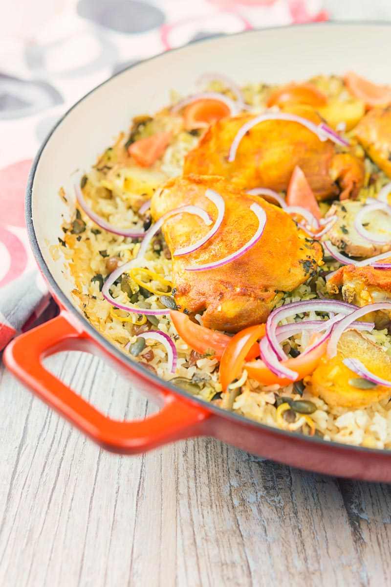 Tall close up image of one pot chicken and rice featuring turmeric chicken thighs and red onion slivers
