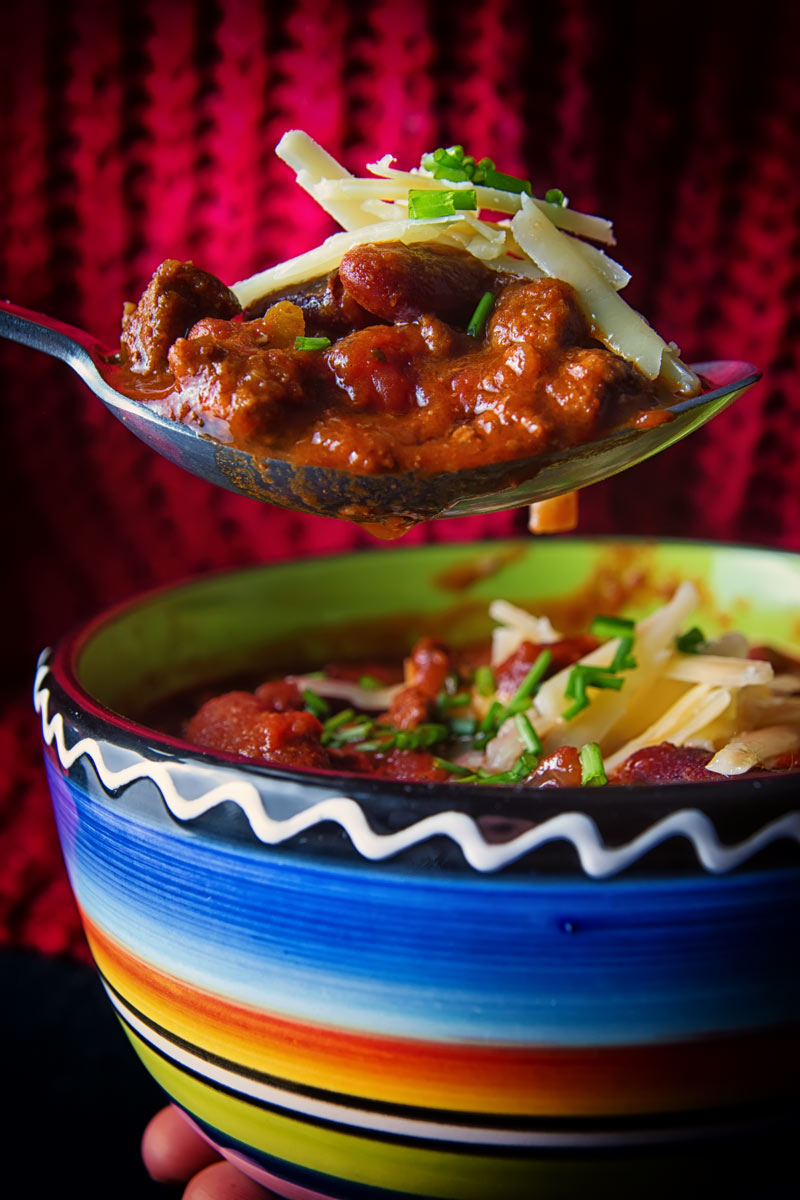 Portrait image of chili con carne topped with sour cream, cheese and chives in a colourful bowl with the dine taking a spoonful