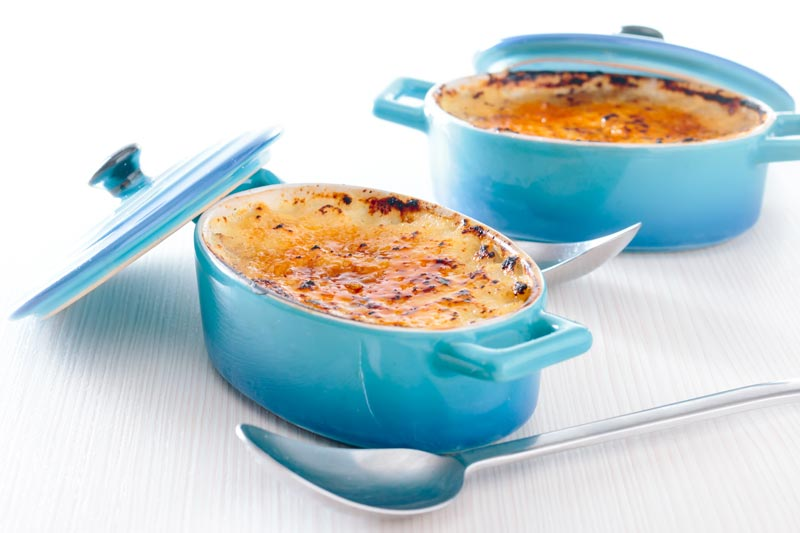 Landscape image of two individual instant pot rice pudding cooked in blue serving pots with a brulee topping