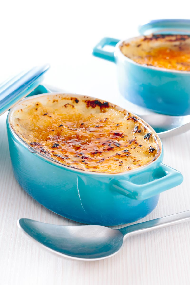 Tall close up image of an individual instant pot rice pudding cooked in blue serving pots with a brulee topping