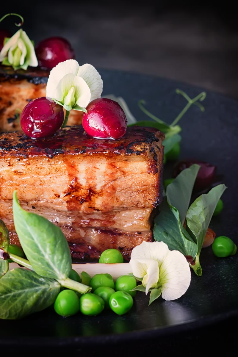 Pressed pork belly with cherries, peas and pea shoots swerved on a black plate