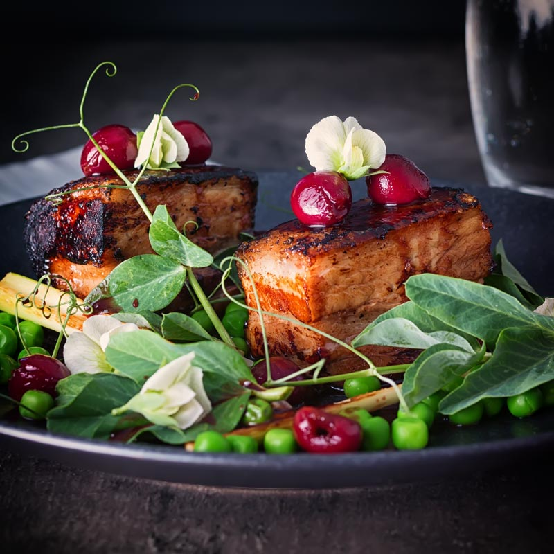 2 slices of pressed pork belly with cherries, peas and pea shoots swerved on a black plate