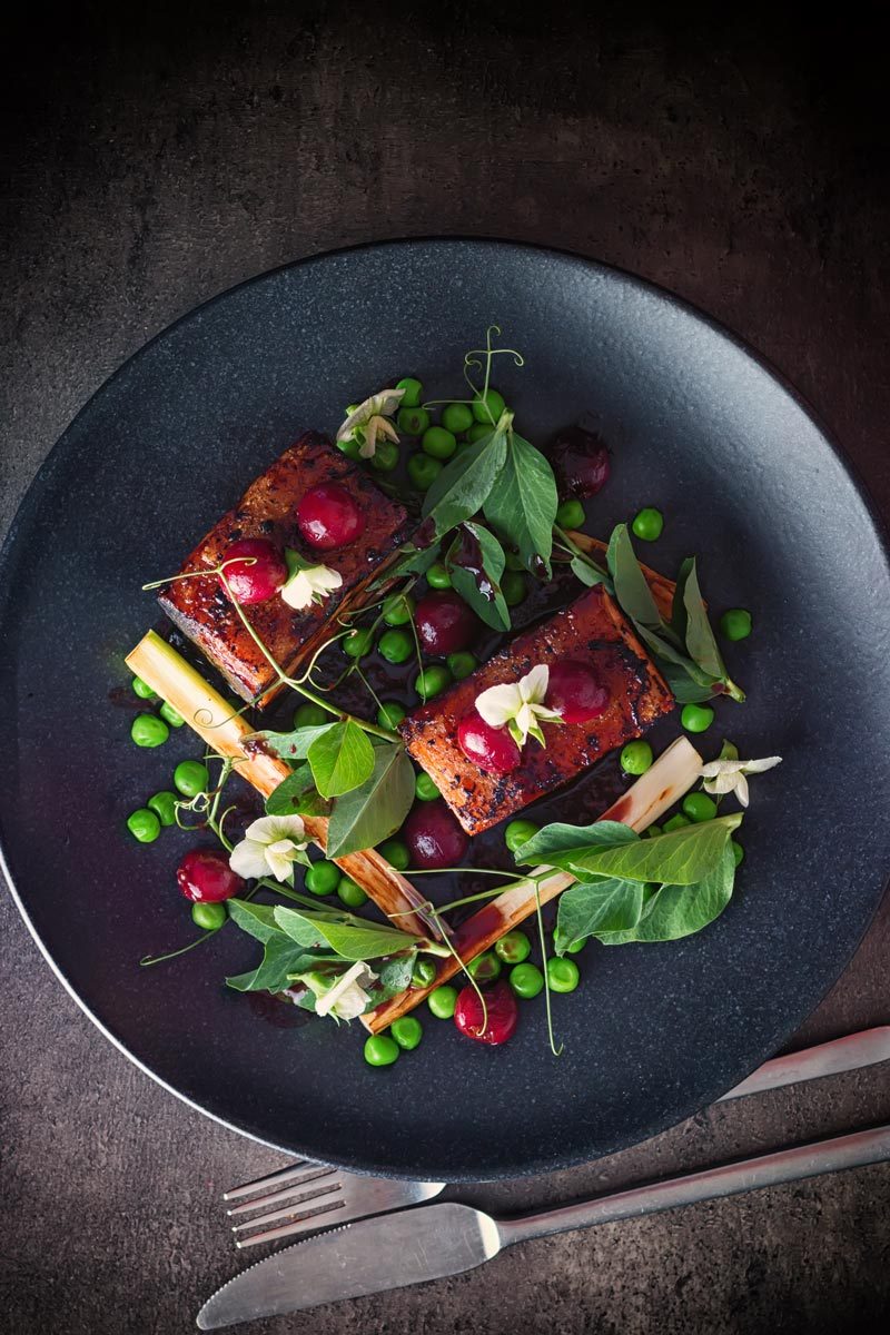 Pressed pork belly with cherries, peas and pea shoots swerved on a black plate photographed from above.
