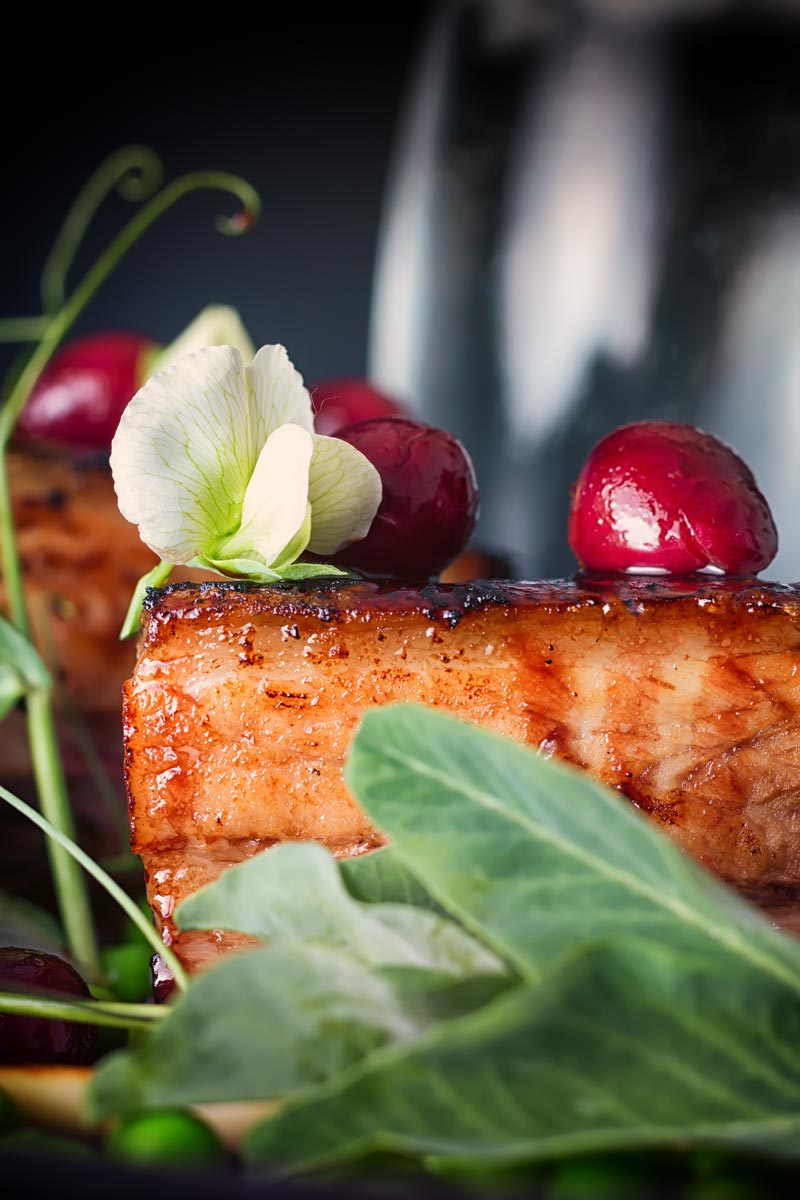 Close up of pressed pork belly with cherries, and pea flowers against a dark backdrop