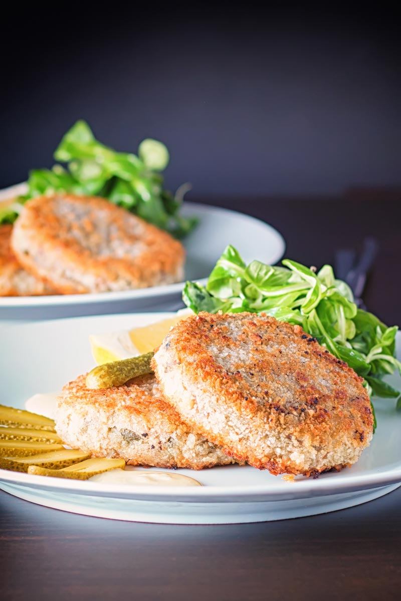 Portrait image of Canned Mackerel fish cakes with pickles on a white plate against a dark backdrop