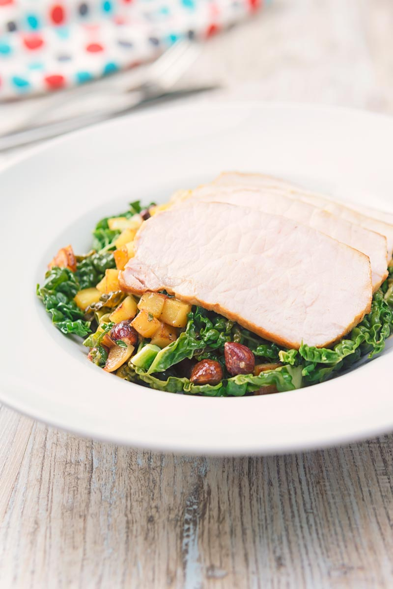Tall image image of mustard roast pork on a bed of cabbage and golden fried potatoes and hazelnuts in a white bowl and spotted linen