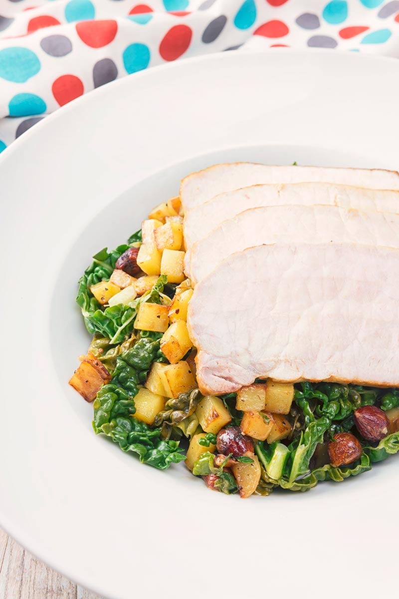 Tall close up image of mustard roast pork on a bed of cabbage and golden fried potatoes and hazelnuts in a white bowl and spotted linen