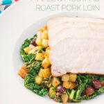 Tall close up image of mustard roast pork on a bed of cabbage and golden fried potatoes and hazelnuts in a white bowl and spotted lined