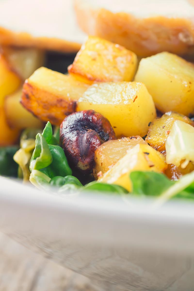 Tall close up image of golden fried potatoes with hazelnuts on a bed of cabbage