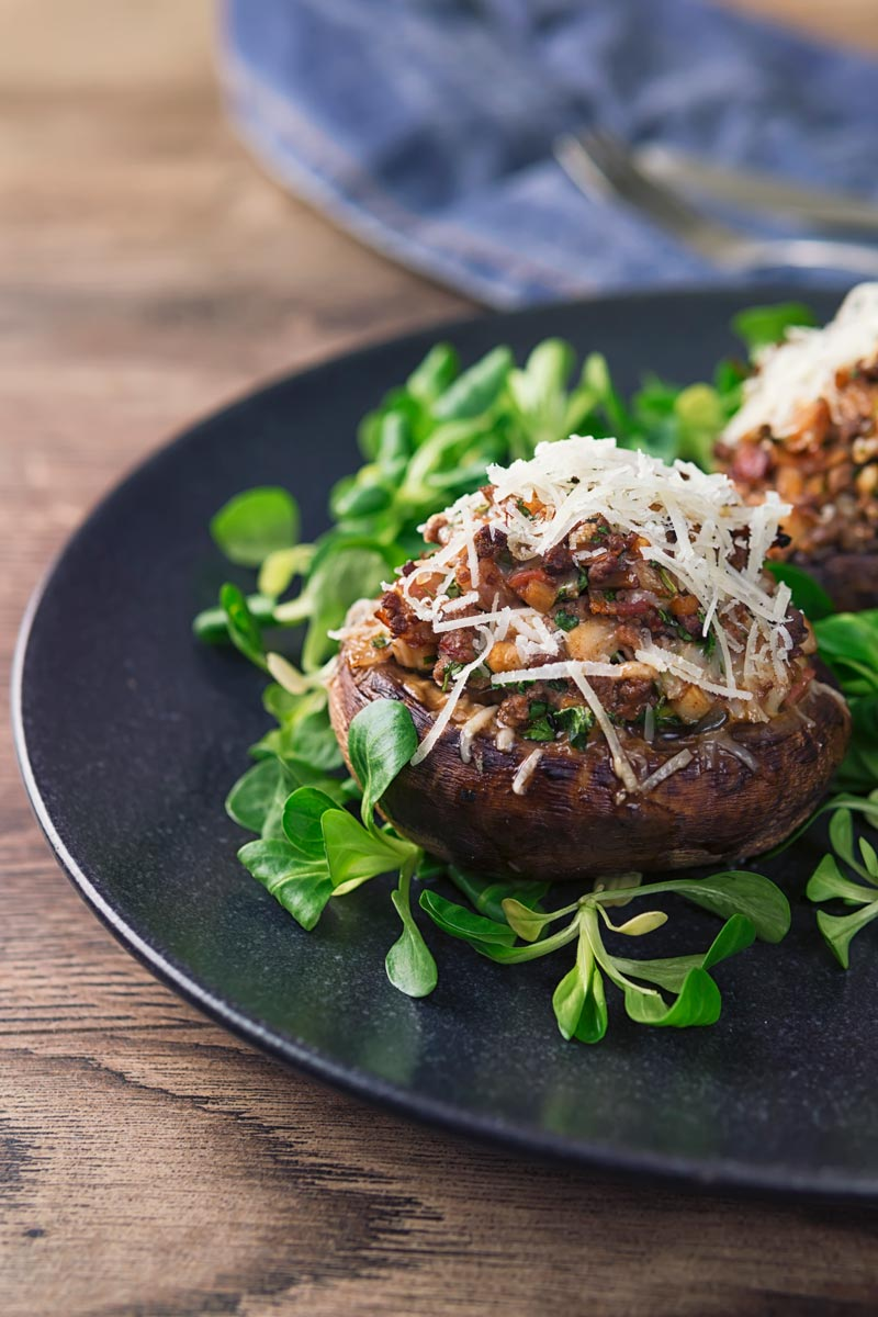 Tall image of a minced beef stuffed mushroom topped with Parmesan cheese on a wooden table