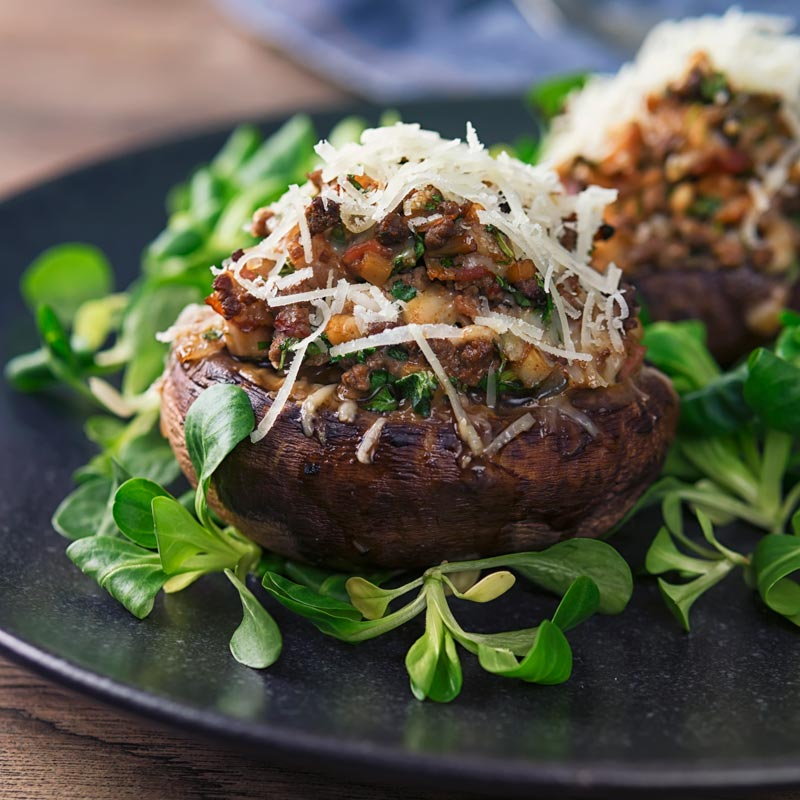 Square image of minced beef stuffed mushrooms with salad laves on a black plate
