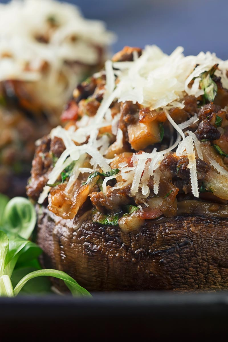 Close up tall image of a minced beef stuffed mushroom topped with Parmesan cheese