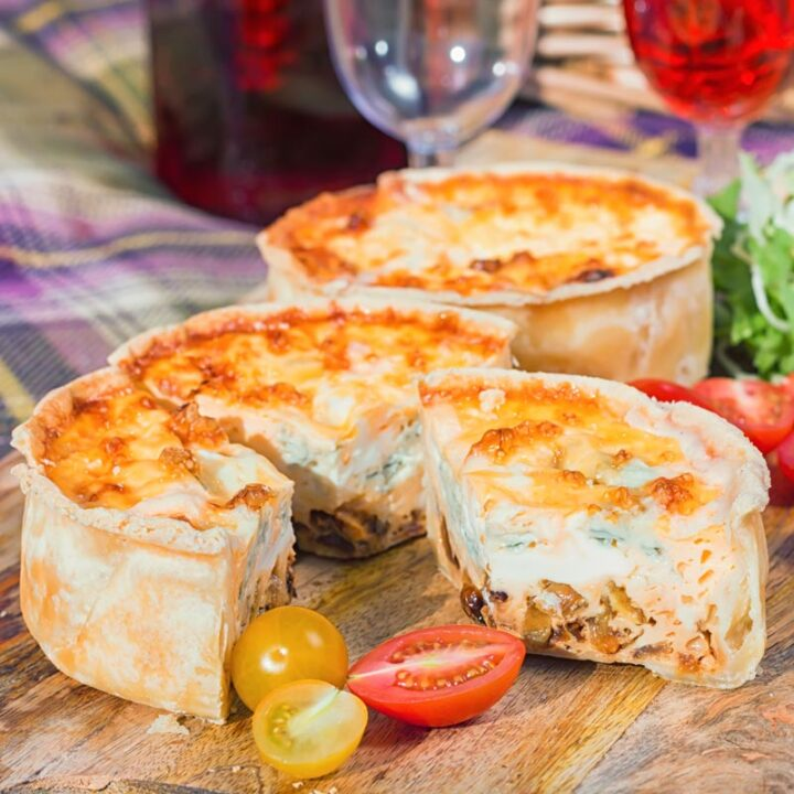 Square image of two mini cheese and onion quiche with one mini quiche cut open on a wooden chopping board in a picnic setting
