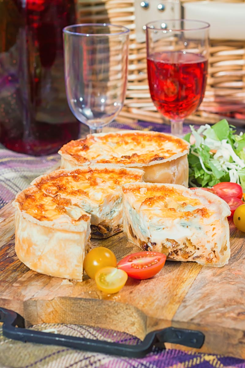 Portrait image of two mini cheese and onion quiche with one mini quiche cut open on a wooden chopping board in a picnic setting