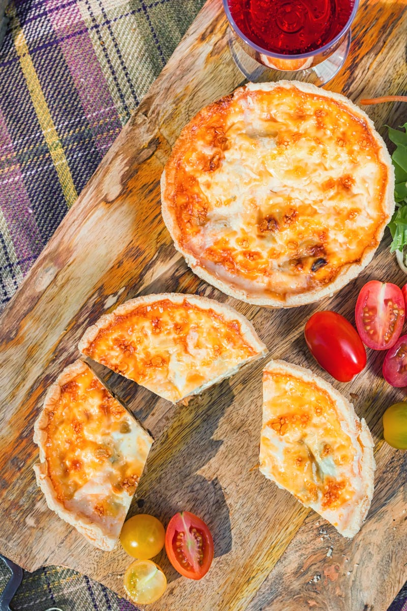 Overhead portrait image of two mini cheese and onion quiche with one mini quiche cut open on a wooden chopping board in a picnic setting
