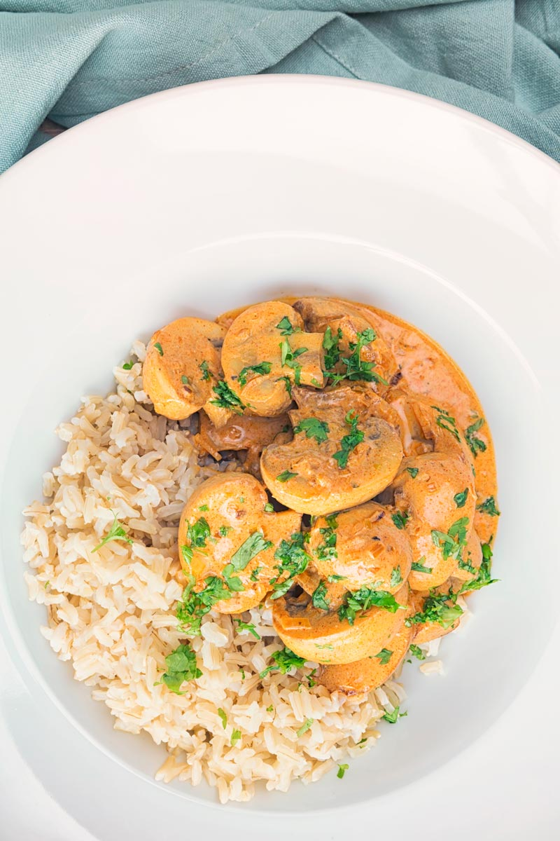 Portrait overhead image of mushroom stroganoff served with wholegrain brown rice served in a white bowl with parsley.