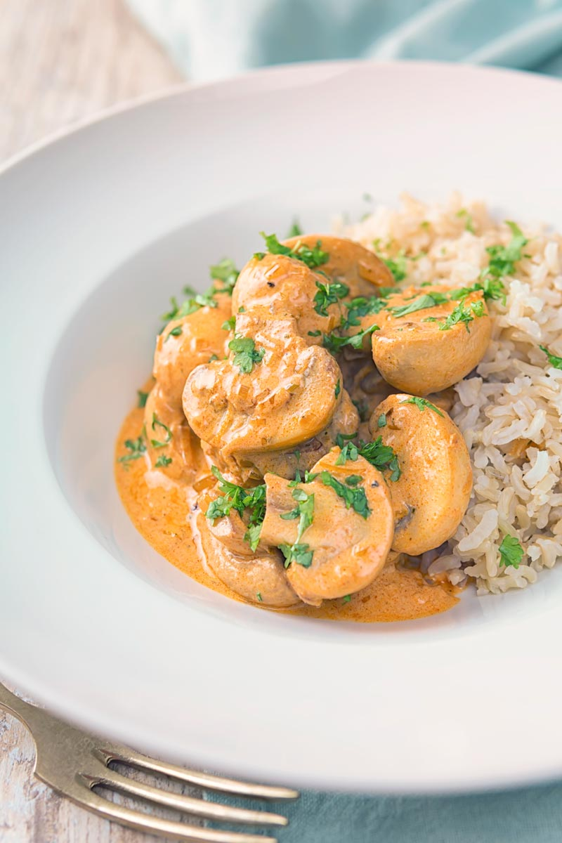 Portrait image of mushroom stroganoff served with wholegrain brown rice served in a white bowl with parsley.