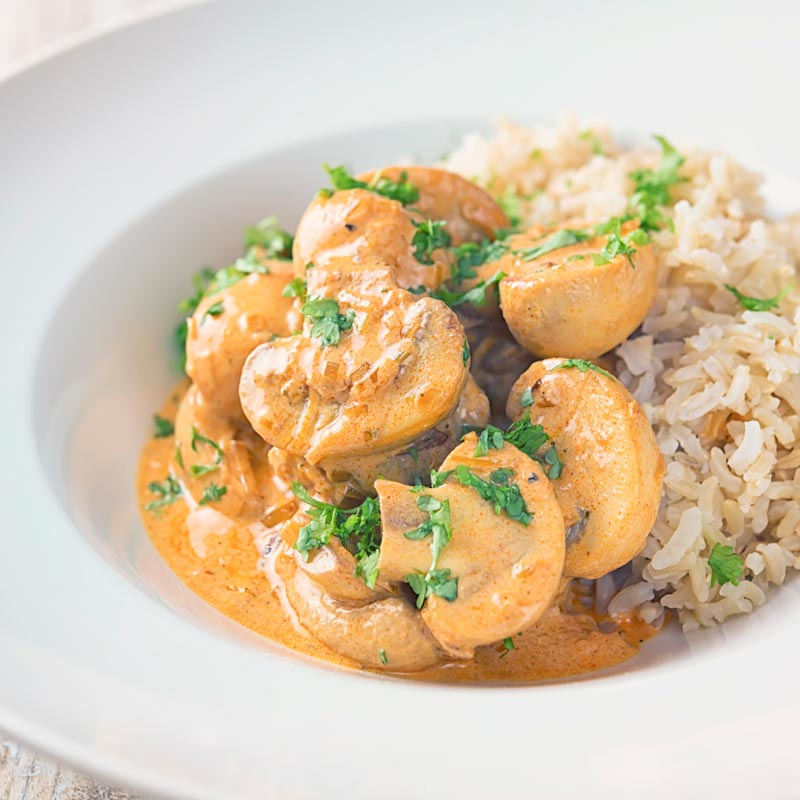 Square image of mushroom stroganoff served with wholegrain brown rice served in a white bowl with parsley.