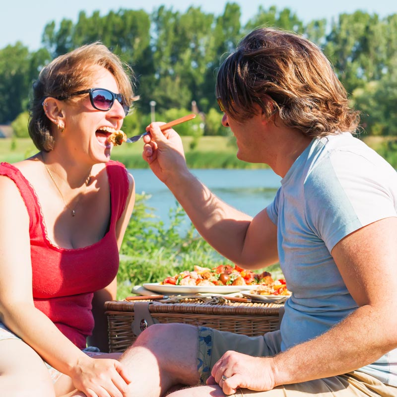 Man feeding woman a fork full of salad in a picnic setting