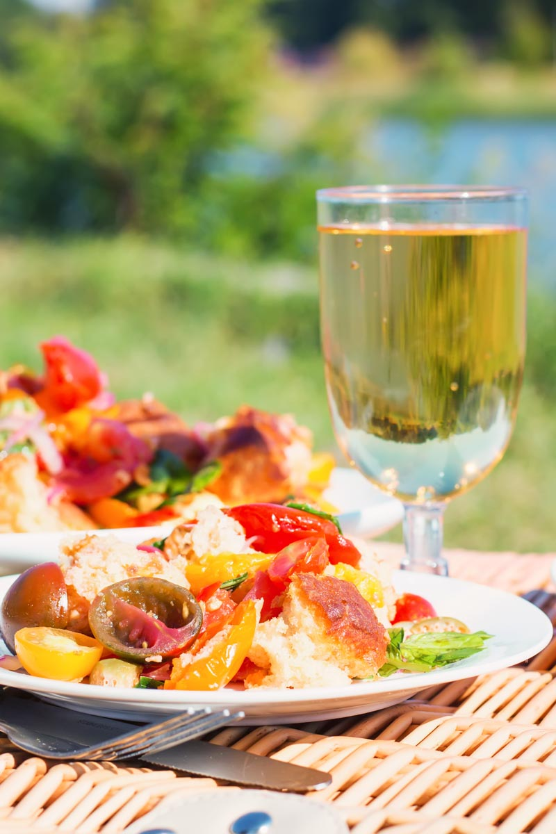 Tall image of a panzanella salad in a lake side setting with a glass of wine