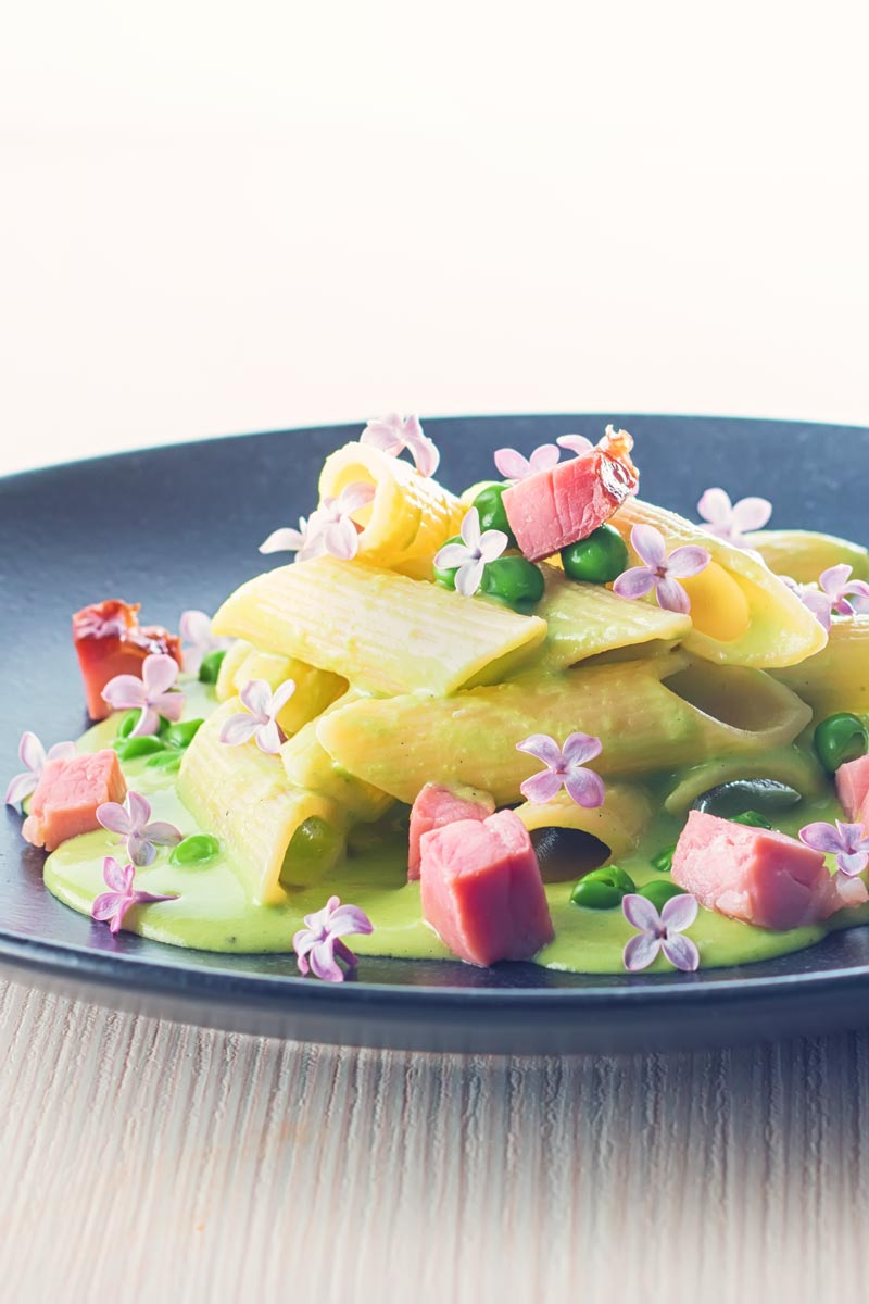 Portrait image of pea and Ham pasta with a pea puree, fresh peas, chunks of ham and lilac edible flowers