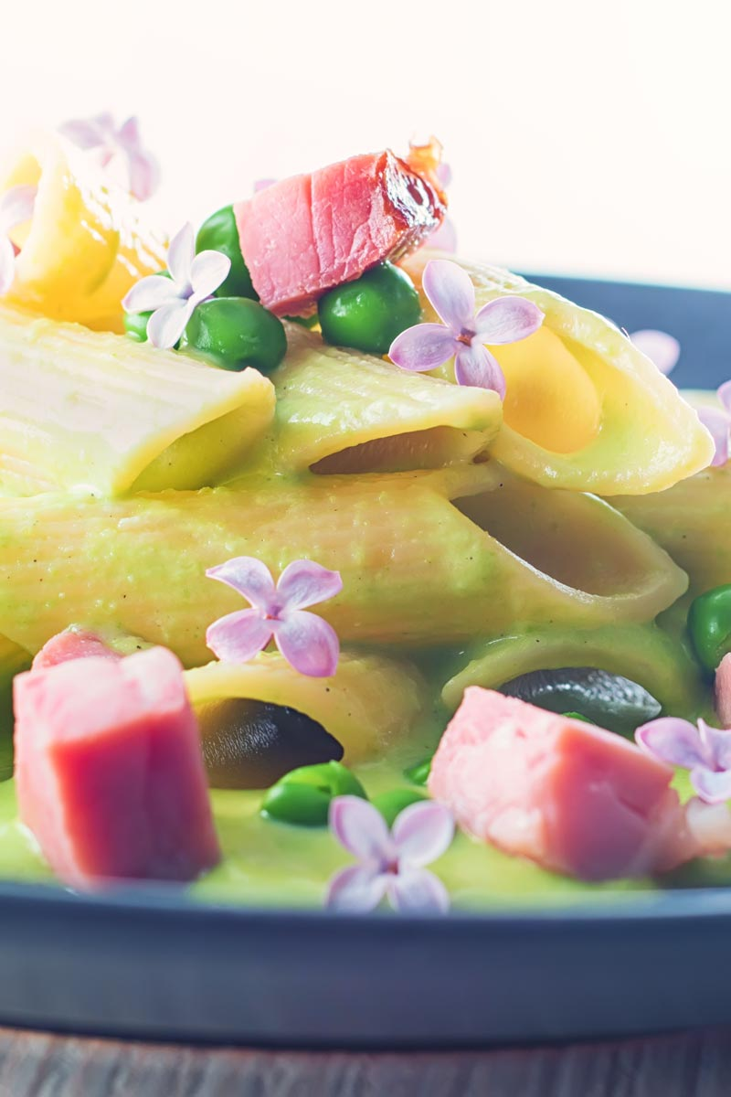 Portrait close up image of pea and Ham pasta with a pea puree, fresh peas, chunks of ham and lilac edible flowers