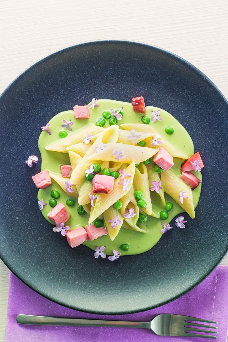 Portrait overhead image of pea and Ham pasta with a pea puree, fresh peas, chunks of ham and lilac edible flowers