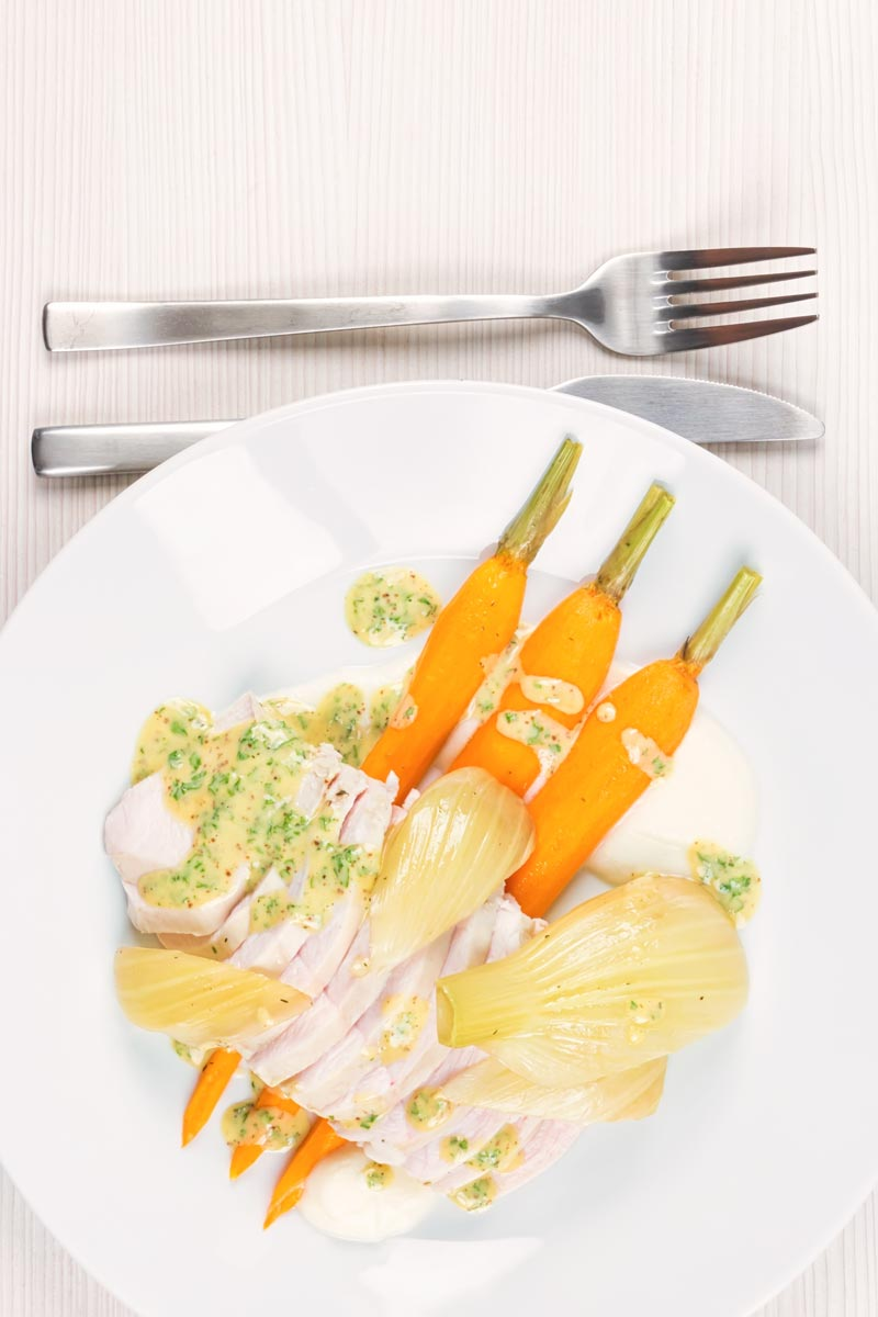 Portrait overhead image of a sliced poached chicken breast on a white plate with carrots, fennel and kohlrabi puree and a mustard sauce