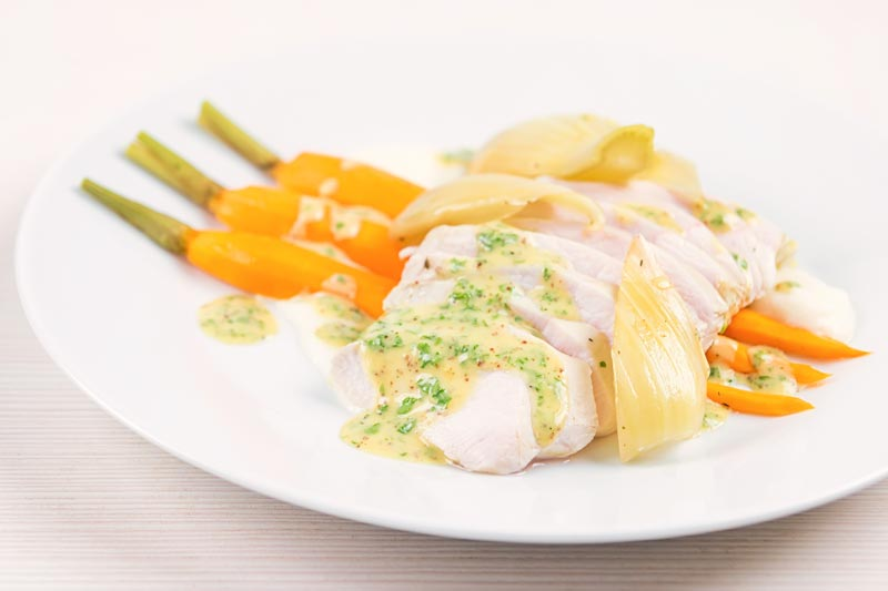 Landscape image of a sliced poached chicken breast on a white plate with carrots, fennel and kohlrabi puree and a mustard sauce