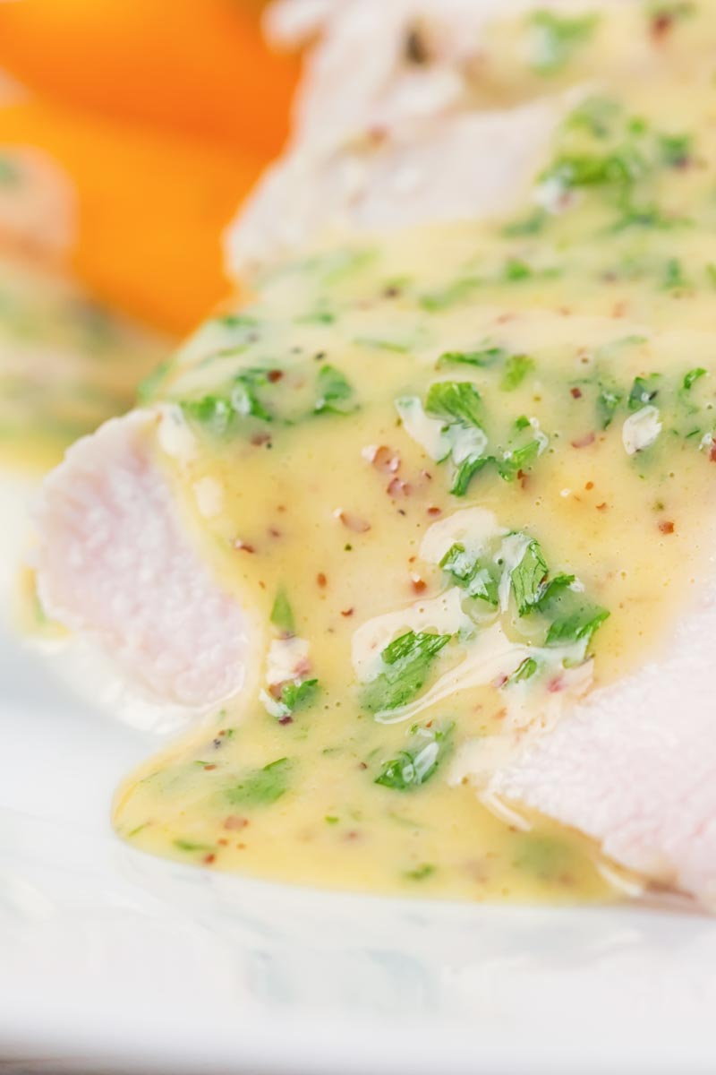 Close up portrait image image of a sliced poached chicken breast on a white plate with a mustard sauce