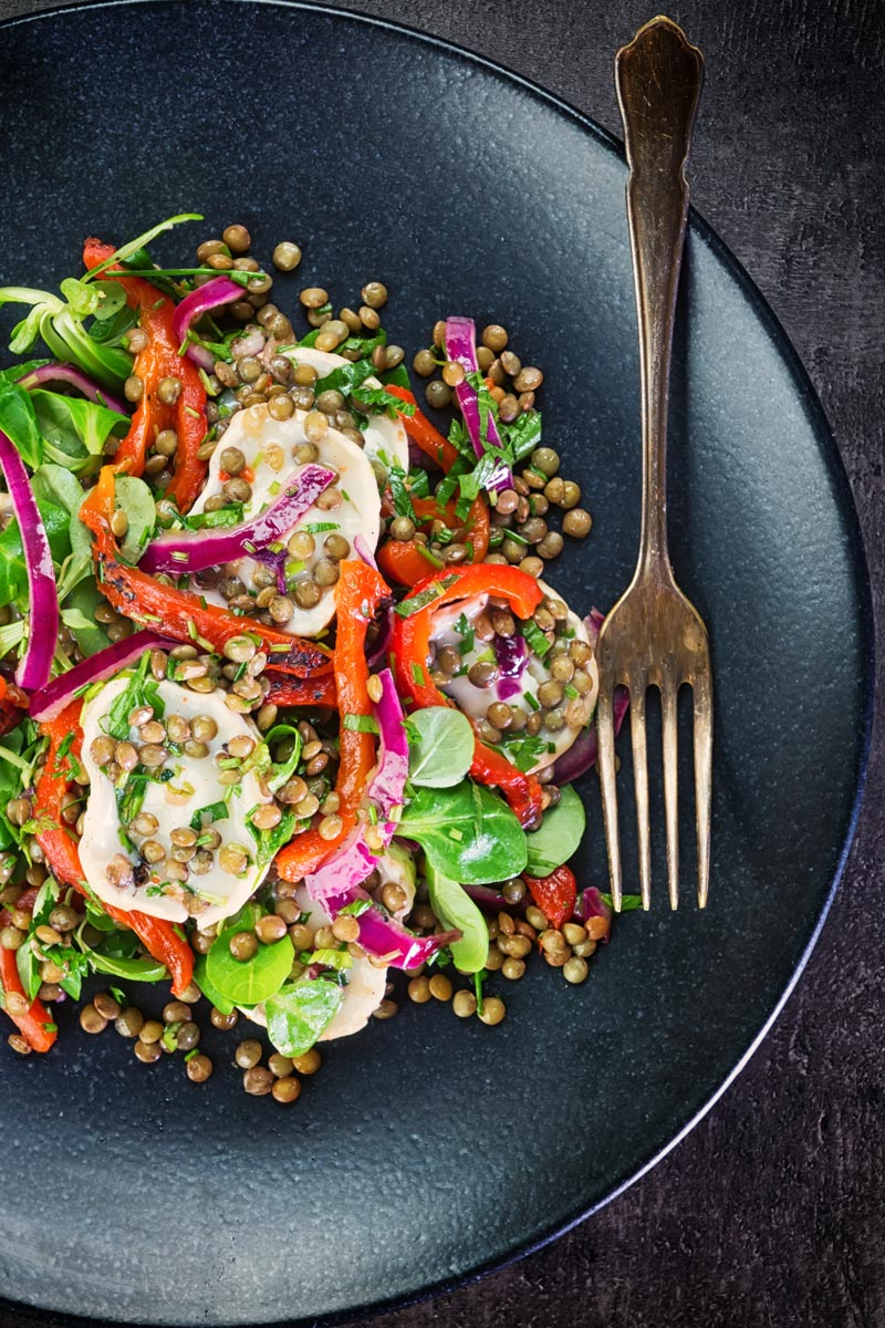 Overhead image of a puy lentil salad with soft goats cheese, red onion and roasted red peppers on a black plate with a vintage fork