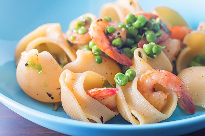 Close up landscape image of a bowl of pea and prawn pasta served in a blue bowl