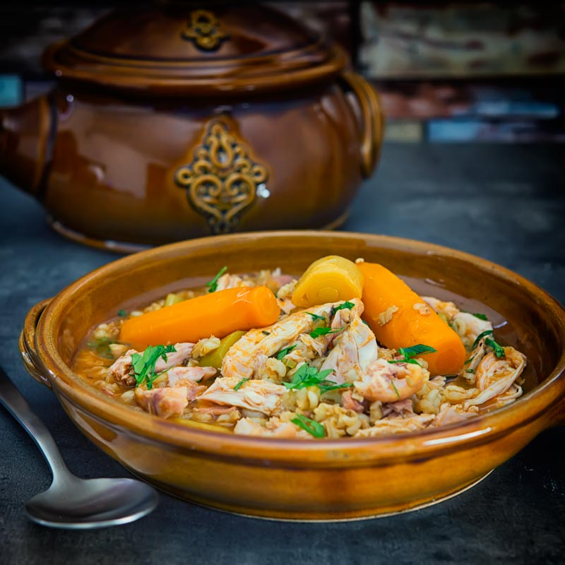 Square image of a rabbit stew with pearly barley in an earthenware bowl and carrots
