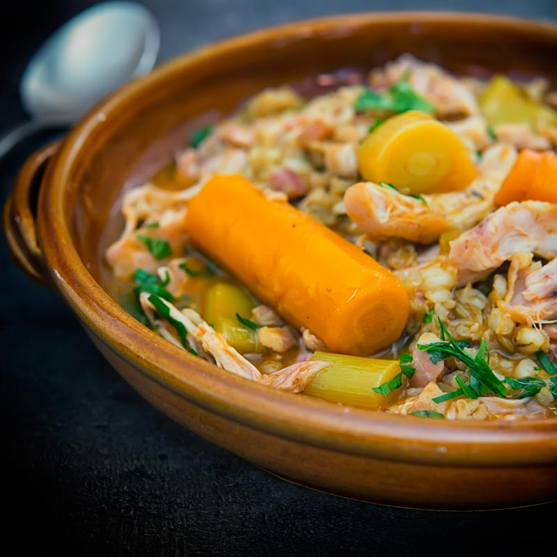 Square close up image of a rabbit stew with pearly barley in an earthenware bowl and carrots
