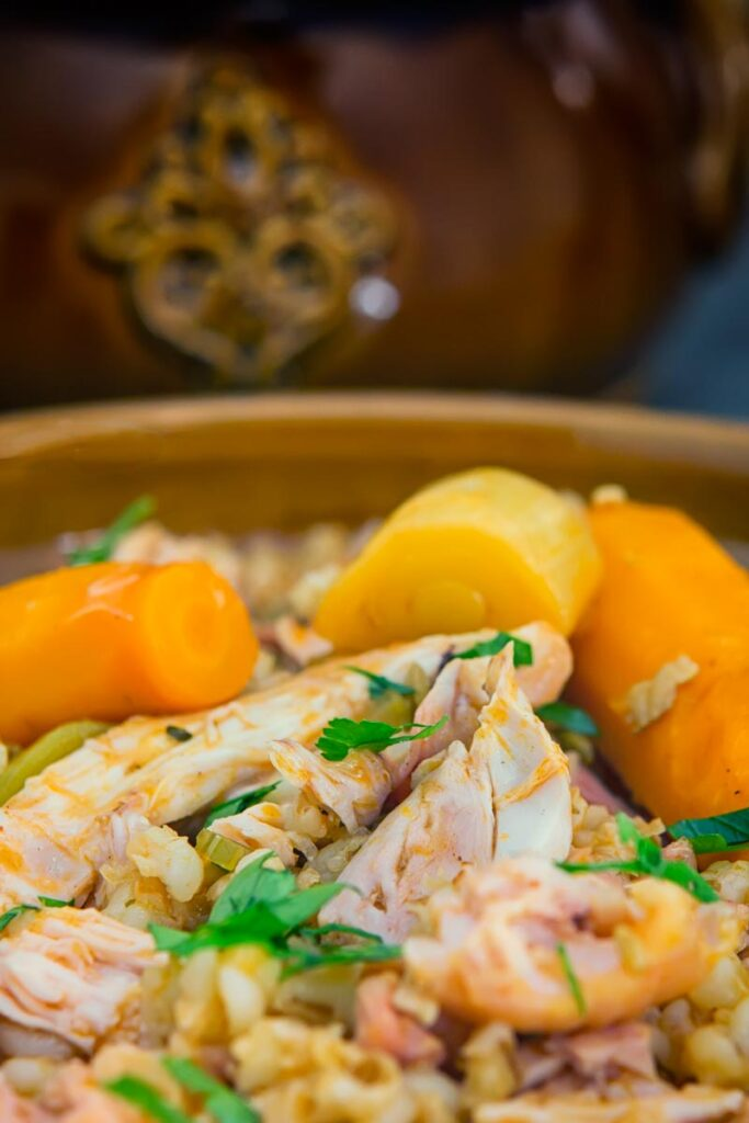 Tall close up image of a rabbit stew with pearly barley in an earthenware bowl and carrots