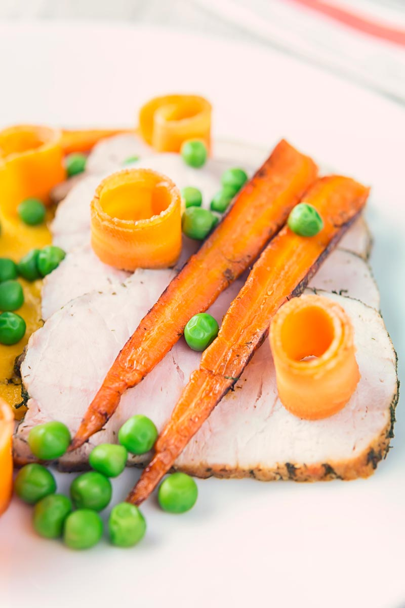 Tall image of roasted pork loin with peas, pickled carrot curls and roasted carrots