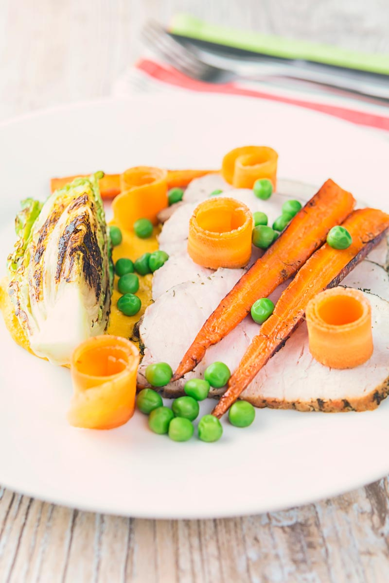 Tall image of roasted pork loin slices with peas, seared lettuce, pickled carrot curls, carrot puree and roasted carrots