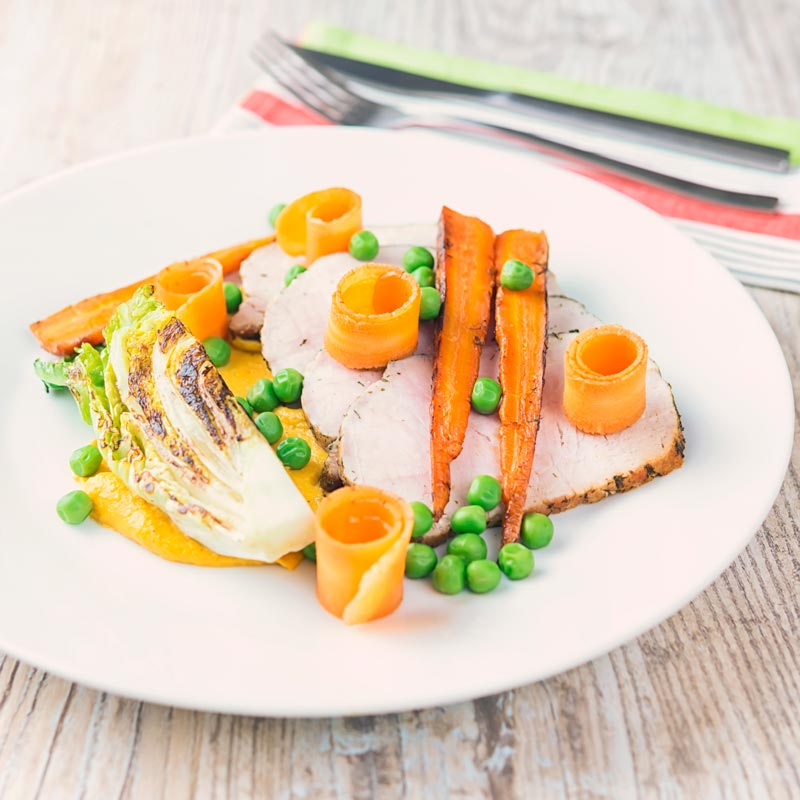 Square image of roasted pork loin slices with peas, seared lettuce, pickled carrot curls, carrot puree and roasted carrots