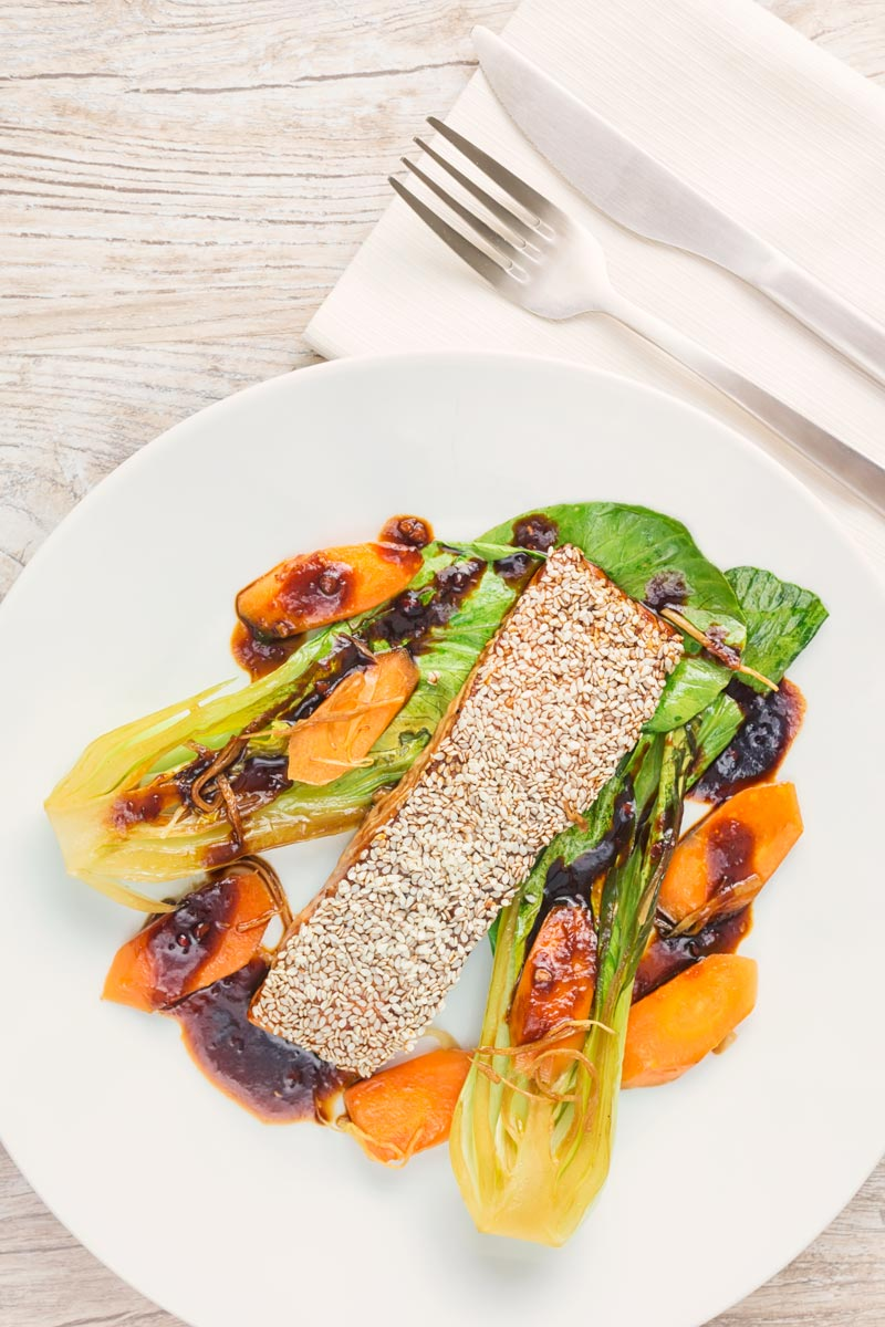 Portrait overhead image of a sesame salmon fillet served with ginger bok choi and carrots on a white plate