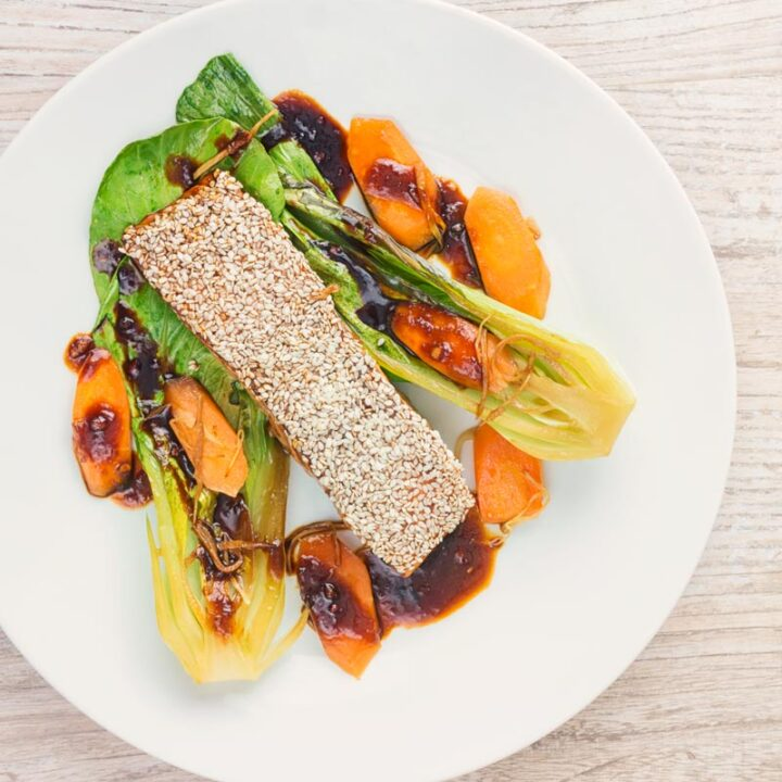Square overhead image of a sesame salmon fillet served with ginger bok choi and carrots on a white plate